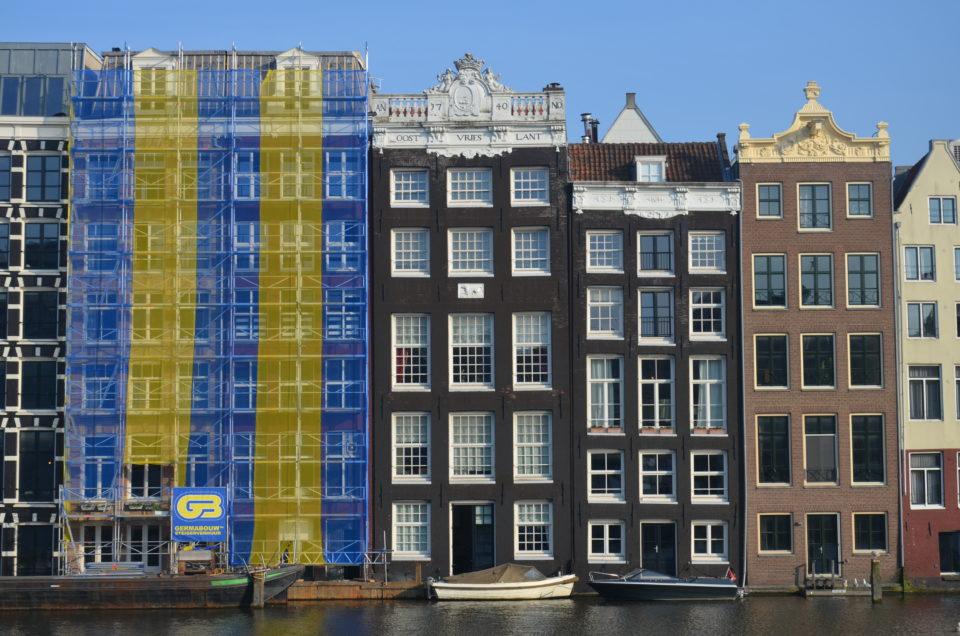 Dein Amsterdam Stadtrundgang führt dich auch an dieser fotogenen Häuserreihe am Damrak vorbei.